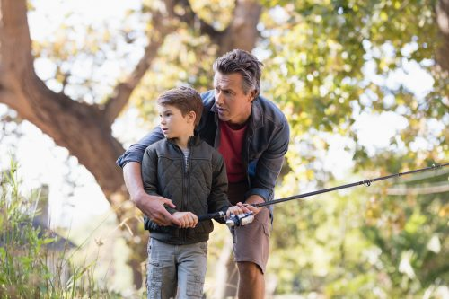 Father and son fishing in forest